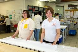 Mitarbeiterinnen der Wäscherei Guben beim Arbeiten an der Mangel.