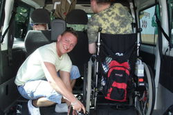Autofahrt mit Mitarbeitern im Rollstuhl.